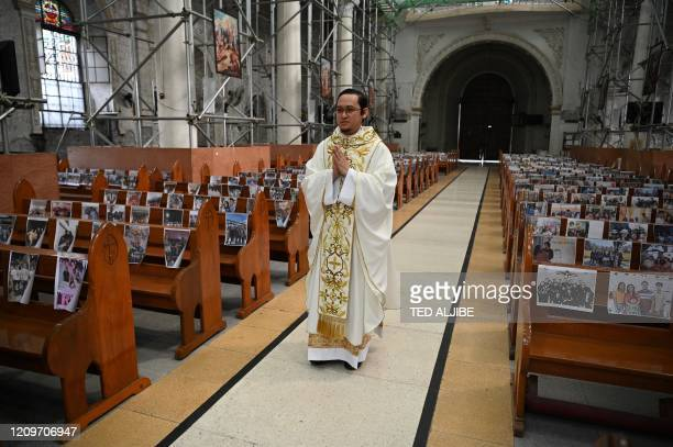 TOPSHOT Roman Catholic priest Reverend Father Mark de Leon walks down the aisle through the empty Holy Rosary parish church with photos of...