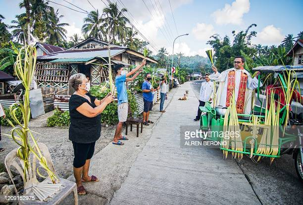A Roman Catholic priest riding on a tricycle and wearing a face mask blesses the faithfuls holding coconut leaves during Palm Sunday event in...