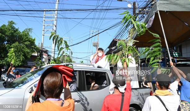 A Roman Catholic priest wearing a face mask atop a pick up truck blesses the faithfuls waving plant leaves during Palm Sunday event in Manila on...