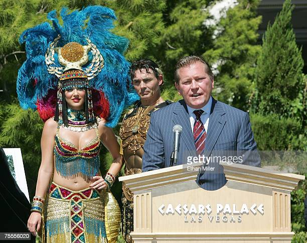 Roman characters Cleopatra and Julius Caesar look on as Caesars Palace general manager John Unwin speaks during a news conference at Caesars July 19...