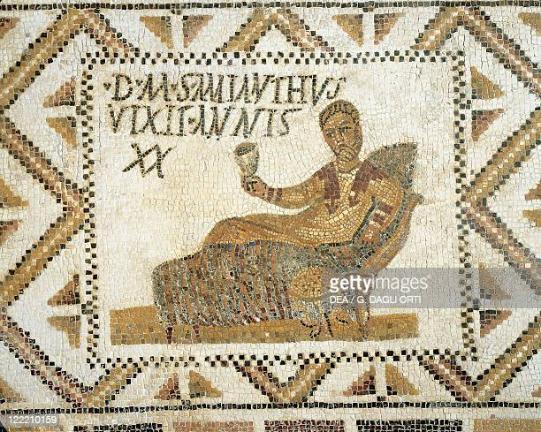 Roman civilization 4th century AD Funerary mosaic depicting a young man drinking while lying on a bed From Henchir Thyna ancient Thaenae Tunisia