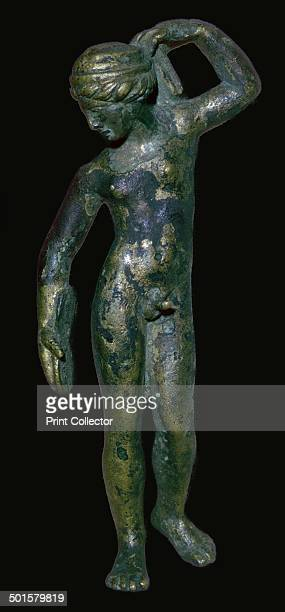 Roman copper alloy figure of a nude male wearing a turban with wavy hair beneath In his right hand he holds an object which might be a jumping weight...