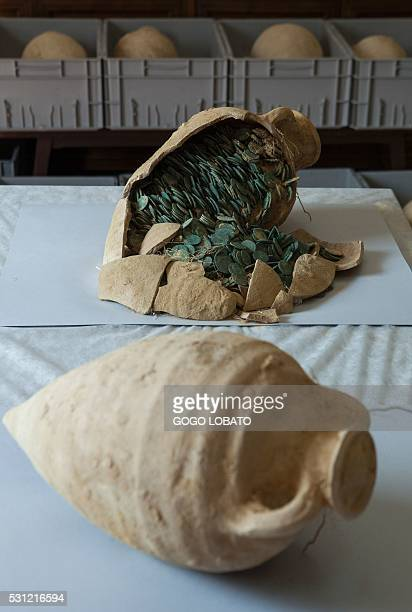 A Roman era amphora filled with bronze coins is displayed at the archaeological museum in Sevilla on April 28 2016 following their discovery during...
