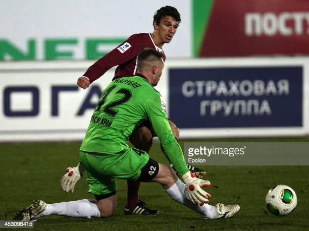Roman Eremenko of FC Rubin Kazan is challenged by Sergei Narubin of FC Amkar Perm during the Russian Football League Championship match between FC...