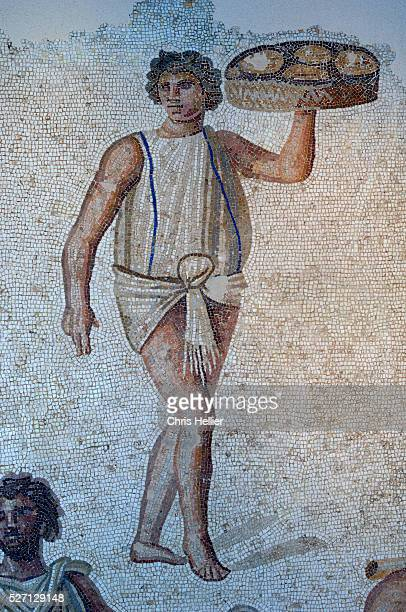 Roman floor mosaic of young slave carrying tray of food for a banquet circa 2nd century AD from Carthage Tunisia