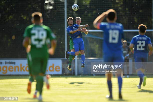 Roman Fuchs of Olching and JanIngwer CallsenBracker of Augsburg jump for a header during the preseason friendly match between SC Olching and FC...