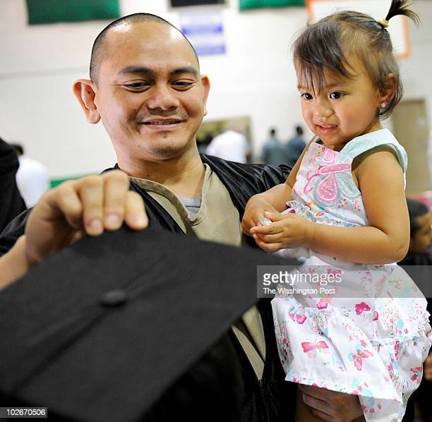 Roman Fuentes places his mortar board on his son Nicholas head while holding his youngest daughter Valentine 2 He was one of 11 inmates at the...