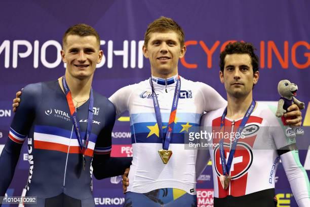 Roman Gladysh of Ukraine celebrates winning gold with silver medallist Adrien Garel of France and bronze medallist Tristan Marguet of Switzerland in...