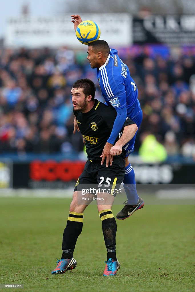 Roman Golobart of Wigan Athletic is beaten to the ball by Matthew Barnes-Homer of Macclesfield Town during the Budweiser FA Cup fourth round match between Macclesfield Town and Wigan Athletic at Moss Rose Ground on January 26, 2013 in Macclesfield, England.