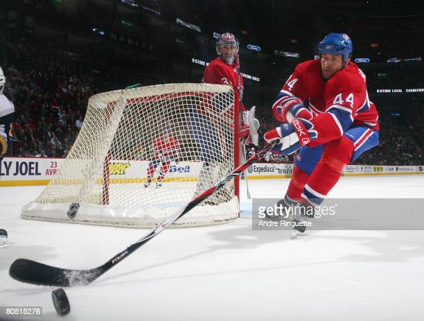 Roman Hamrlik of the Montreal Canadiens reaches for a loose puck along the boards behind the net of teammate Carey Price against the Buffalo Sabres...