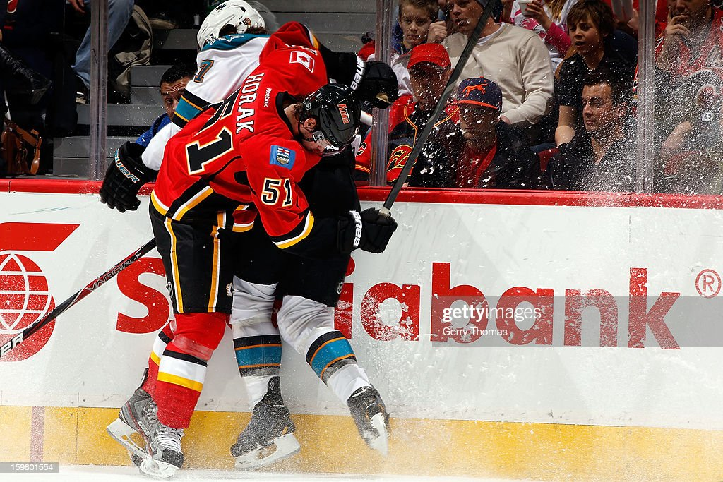 Roman Horak #51 of the Calgary Flames checks Brad Stuart #7 of the San Jose Sharks on January 20, 2013 at the Scotiabank Saddledome in Calgary, Alberta, Canada.