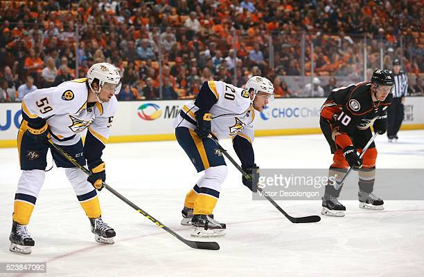 Roman Josi and Miikka Salomaki of the Nashville Predators line up at the edge of the faceoff cirlce against Corey Perry of the Anaheim Ducks in the...