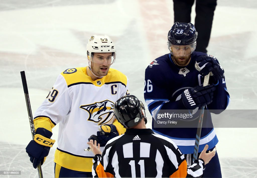 Roman Josi #59 of the Nashville Predators and Blake Wheeler #26 of the Winnipeg Jets listen to an explanation of a call by referee Kelly Sutherland #11 during a second period stoppage in play at the Bell MTS Place on February 27, 2018 in Winnipeg, Manitoba, Canada.