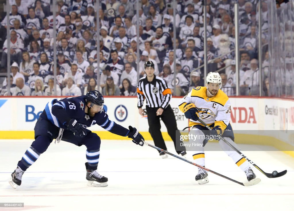 Roman Josi #59 of the Nashville Predators chips he puck down the ice past a defending Blake Wheeler #26 of the Winnipeg Jets during third period action in Game Four of the Western Conference Second Round during the 2018 NHL Stanley Cup Playoffs at the Bell MTS Place on May 3, 2018 in Winnipeg, Manitoba, Canada.