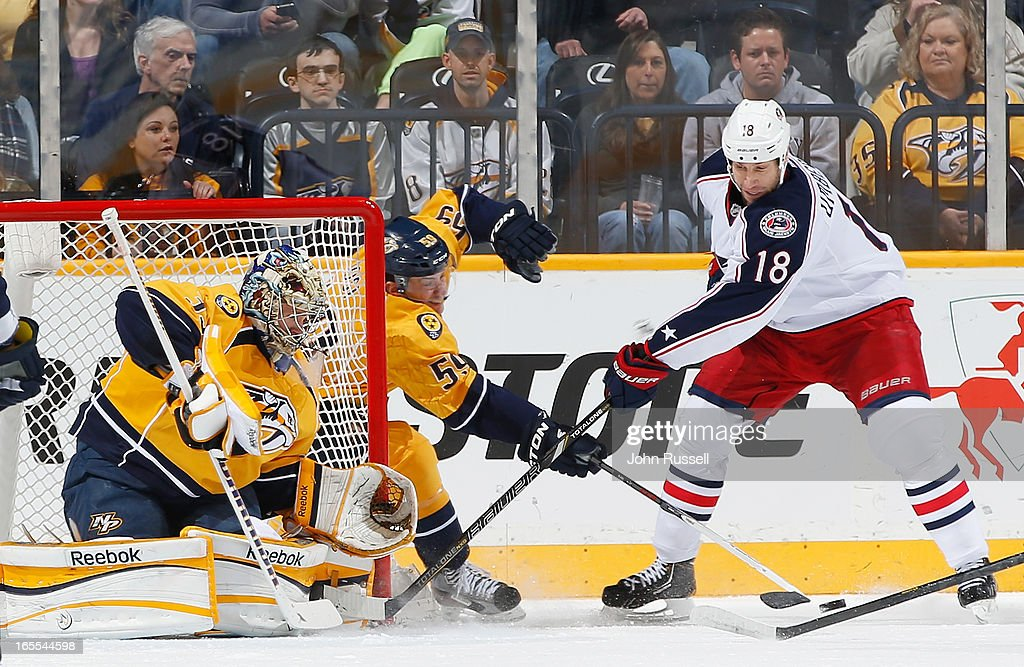 Roman Josi #59 of the Nashville Predators clears the puck against RJ Umberger #18 of the Columbus Blue Jackets during an NHL game at the Bridgestone Arena on April 4, 2013 in Nashville, Tennessee.