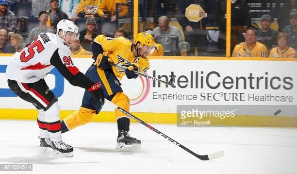 Roman Josi of the Nashville Predators shoots the puck against Matt Duchene of the Ottawa Senators during an NHL game at Bridgestone Arena on February...