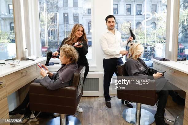 Roman K Salon owner Roman Kusayev styles Orfeh's hair at the Roman K Salon Madison Avenue Opening on November 21 2019 in New York City