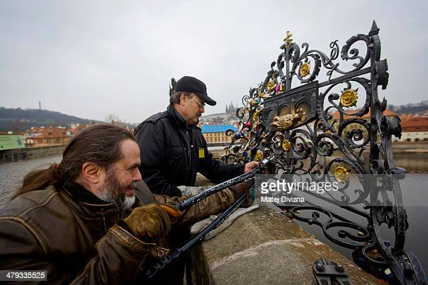 Roman Kotrc from Charles Bridge Artists Association with the aid of security guard remove love padlocks from Charles Bridge on March 18 2014 in...