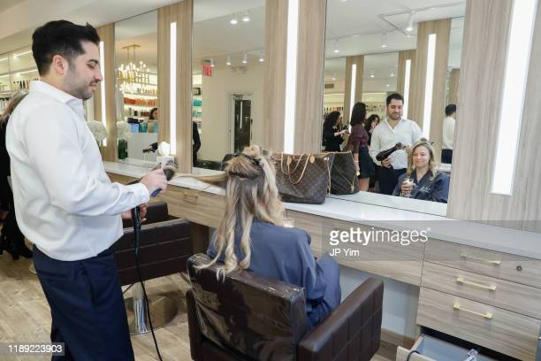 Roman Kusayev styles a client's hair at the Roman K Salon Madison Avenue Opening on November 21 2019 in New York City