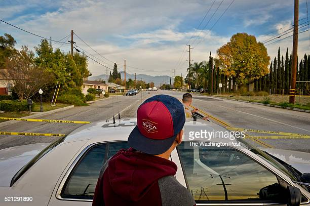 Roman Lecona looks over a police cruiser on San Bernardino Ave Thursday afternoon before being escorted to his home in the active crime scene where a...