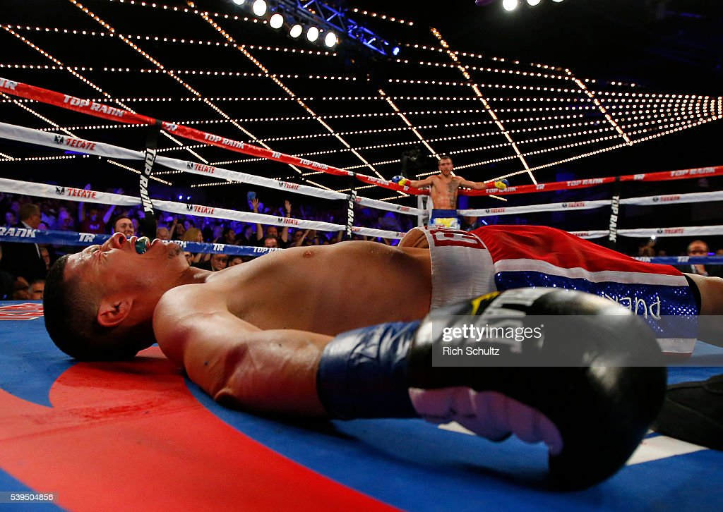Roman Martinez is knocked out as Vasyl Lomachenko raises his arms in the neutral corner during the fifth round of their Junior Lightweight WBO World Championship bout on June 11, 2016 at the Theater at Madison Square Garden in New York City.