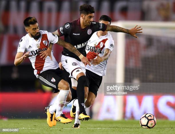 Roman Martinez of Lanus fights for the ball with Ariel Rojas and Enzo Perez of River Plate during a first leg match between River Plate and Lanus as...