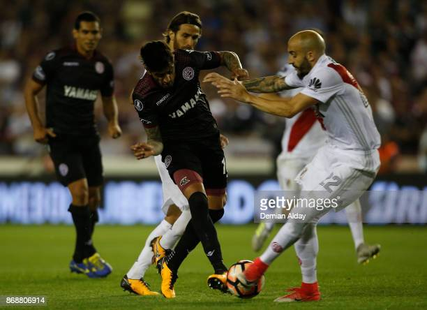 Roman Martinez of Lanus fights for the ball with Javier Pinola of River Plate during a second leg match between Lanus and River Plate as part of the...