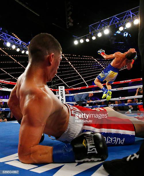 Roman Martinez watches as Vasyl Lomachenko does a backflip after knocking Martinez out during the fifth round of their Junior Lightweight WBO World...