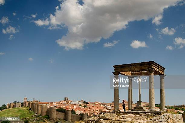 Roman monument 'Los Cuatro Postes' with town walls in background.