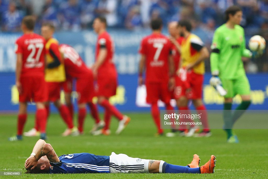 Roman Neustadter of Schalke on the ground looks dejected after the referee blows the whistle signaling the end of the game during the Bundesliga match between FC Schalke 04 and FC Augsburg held at Veltins-Arena on May 7, 2016 in Gelsenkirchen, Germany.