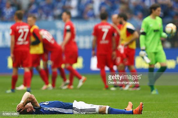 Roman Neustadter of Schalke on the ground looks dejected after the referee blows the whistle signaling the end of the game during the Bundesliga...