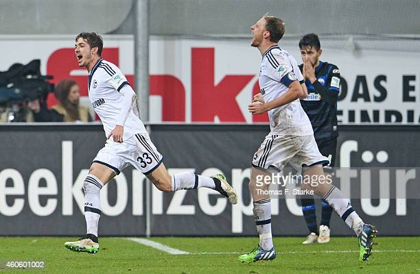 Roman Neustaedter and Benedikt Hoewedes of Schalke celebrate their teams second goal while Lukas Rupp of Paderborn looks dejected during the...