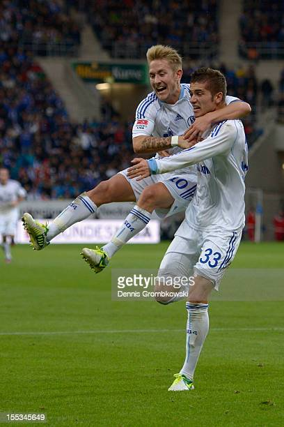 Roman Neustaedter of Schalke celebrates with teammate Lewis Holtby after scoring his team's first goal during the Bundesliga match between TSG 1899...