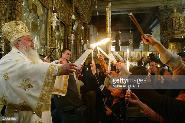 Roman Orthodox Bishop Theophylaktos distributes the holy light to Palestinian Christians as part of the Easter celebrations during the holy Saturday...