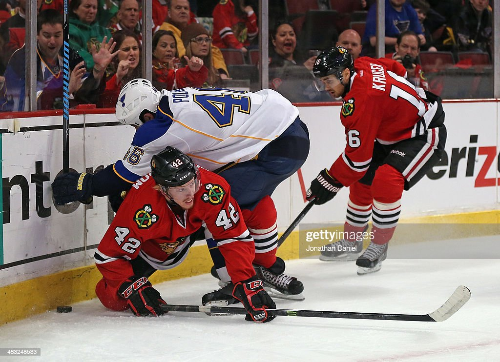 Roman Polak #46 of the St. Louis Blues knocks down Joakim Nordstrom #42 of the Chicago Blackhawks as they battle for the puck and as Marcus Kruger #16 comes in to help at the United Center on April 6, 2014 in Chicago, Illinois. The Blackhawks defeated the Blues 4-2.