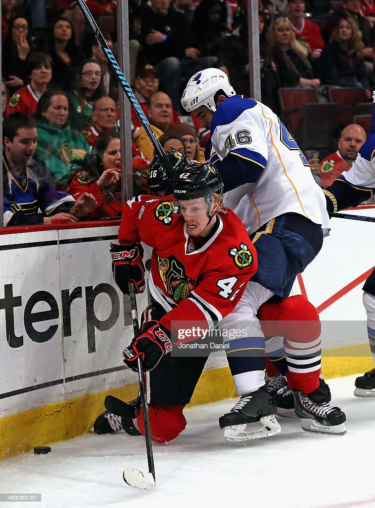 Roman Polak #46 of the St. Louis Blues tries to hold back Joakim Nordstrom #42 of the Chicago Blackhawks with his leg as they battle for the puck at the United Center on April 6, 2014 in Chicago, Illinois.