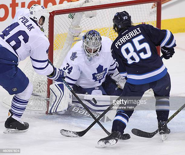Roman Polak of the Toronto Maple Leafs and Mathieu Perreault of the Winnipeg Jets battle for the puck in front of goaltender James Reimer in first...