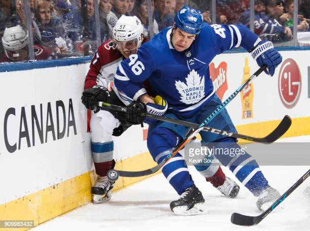 Roman Polak of the Toronto Maple Leafs battles for the puck against Gabriel Bourque of the Colorado Avalanche during the third period at the Air...
