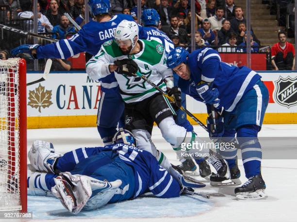 Roman Polak of the Toronto Maple Leafs checks Alexander Radulov of the Dallas Stars into Frederik Andersen during the first period at the Air Canada...