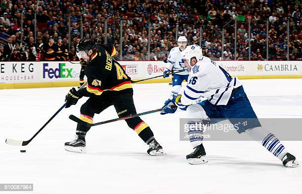 Roman Polak of the Toronto Maple Leafs checks Sven Baertschi of the Vancouver Canucks during their NHL game at Rogers Arena February 13 2016 in...