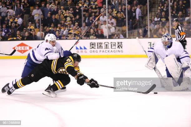 Roman Polak of the Toronto Maple Leafs defends Brad Marchand of the Boston Bruins during the first period of Game Seven of the Eastern Conference...