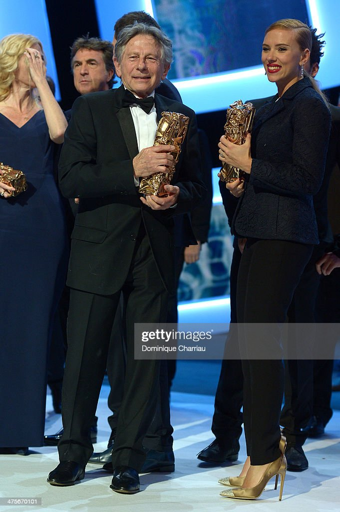 Roman Polanski holds the Best Director award for 'Venus in Fur' while actress Scarlett Johansson holds the Honorary Cesar award on stage during the 39th Cesar Film Awards 2014 at Theatre du Chatelet on February 28, 2014 in Paris, France.