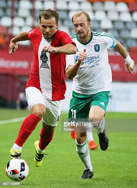 Roman Shishkin of FC Lokomotiv Moscow challenged by Oleksandr Kasyan of FC Tom Tomsk during the Russian Premier League match between FC Lokomotiv...