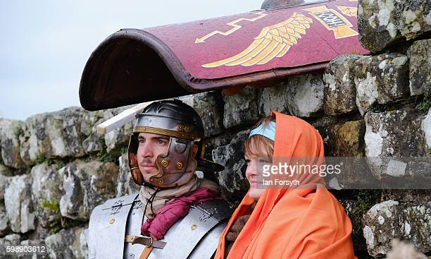 Roman soldier and his wife shelter from rain under a shield as the lives of Roman Legionnaires are reenacted during the Hadrian's Wall Live event at...