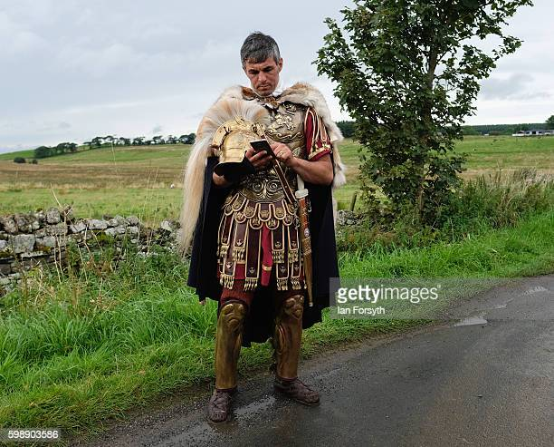 Roman soldier checks his mobile phone as the lives of Roman Legionnaires are reenacted during the Hadrian's Wall Live event at Housesteads Roman fort...