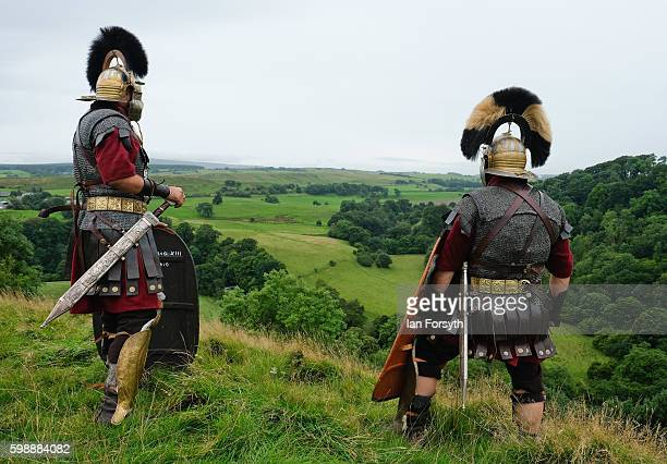Roman soldiers stand guard looking out over the countryside of Cumbria from the Birdoswald Roman Fort as the lives of Roman Legionnaires are...