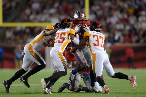 Roman Tatum and Arrion Springs of the LA Wildcats tackle Sammie Coates of the Houston Roughnecks during the XFL game at TDECU Stadium on February 8...