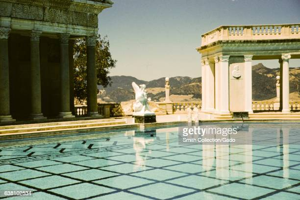 A Roman Temple facade a statue and a marble pavilion sit at the edge of the Neptune Pool at Hearst Castle San Simeon California 1960
