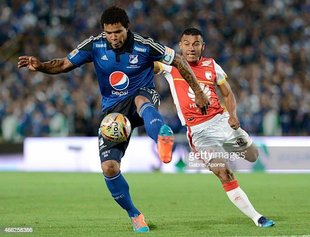 Roman Torres of Millonarios struggles for the ball with Wilson Morelo of Santa Fe during a match between Millonarios and Santa Fe as part of 10th...