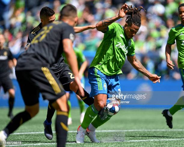 Roman Torres of the Seattle Sounders traps the ball and the foot of Eduard Atuesta of the Los Angeles FC during the second half of the match at...